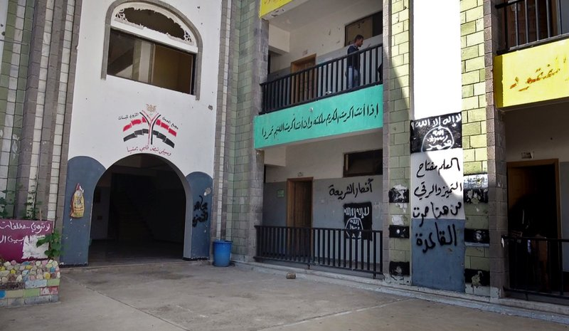"The black al-Qaida flag and the slogan in Arabic ""al-Qaida passed here,"" on the right wall, are sprayed on a damaged school that was turned into a religious court in the southern city of Taiz."