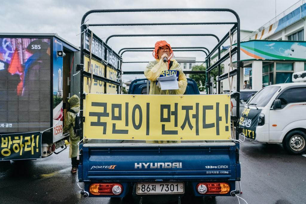 "An anti-immigrant protester in Jeju. The banner reads, ""Koreans First!"""
