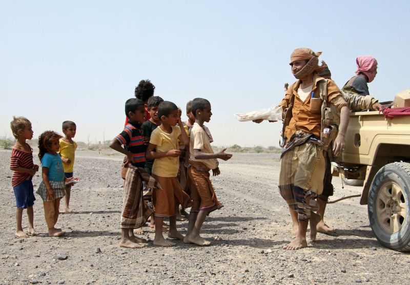 Pro-government fighters provide food to Yemeni children on a road leading to the southwestern city of Mokha on January 26, 2017